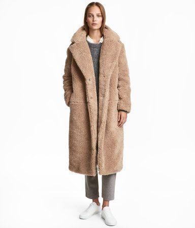 Beige. Langer Mantel aus Teddyfleece. Modell mit Kragen, Revers und verdeckter Druckknopfleiste vorn. Seitliche Nahttaschen. Gefüttert.