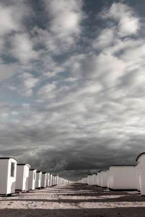 Foto Factory - Fotografi af strandhuse på Løkken strand i Nordjylland fra HjemmeLiv.dk. Fotografiet er taget en sen eftermiddag, hvor skyerne har samlet sig over stranden. Plakaten passer perfekt i stuen i en flot ramme.