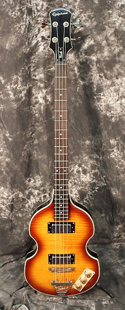 """This veteran from the British invasion is back without the vintage price tag! Mod looks and warm, bass tone come together as a result of its hollow laminated maple body with a short-scale 30"""" maple neck, elegant flamed maple top and dual bass mini-humbucking pickups. Other features include a floating rosewood bridge with trapeze tailpiece, 2 volumes, 1 tone, chrome hardware, and vintage sunburst finish. Excellent condition, finish flaw on back. Case not included. FEATURES  Style: ho..."""
