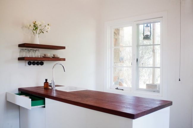 """KITCHEN LOVE: """"The kitchen is up at The Store,"""" says Tracy. """"We were very bound by space there and really people just need to be able to make their breakfast (unless they want to brave eating with my family!), re-heat meals if it is staff living up there during seasonal busy times. The timber bench top and floating jarrah shelves are from farm timber our builder laminated together. The cabinetry is by Darren Gibsone of DG Cabinets. Photo Sally Mills."""