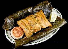 Colombian Tamal. A tamale is a traditional dish made of masa , which is steamed or boiled in a leaf wrapper. In Colombia, they are wrapped in plantain leaves. May contain large pieces of cooked carrot or other vegetables, whole corn kernels, rice, chicken on the bone and/or chunks of pork.