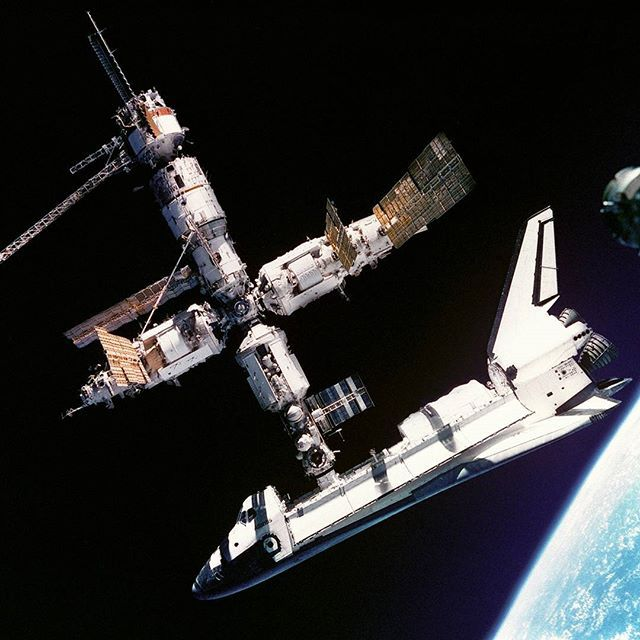 explorenasa One of NASA's coolest pictures ever to kick off the weekend! This view of the Space Shuttle Atlantis still connected to Russia's Mir Space Station was photographed by the Mir-19 crew on July 4, 1995. Cosmonauts Anatoliy Y. Solovyev and Nikolai M. Budarin, Mir-19 Commander and Flight Engineer, respectively, temporarily undocked the Soyuz spacecraft from the cluster of Mir elements to perform a brief fly-around. They took pictures while the STS-71 crew, with Mir-18's three crew…