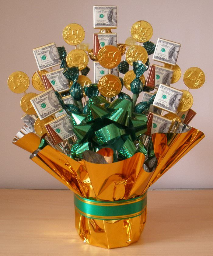 This Money Candy Bouquet turned out pretty cute. You will need some chocolate coins and candies in green wrappers. Secure candy pieces to the skewers and then insert them in in the container with floral foam. Wrap the container in gold cello/tissue paper.