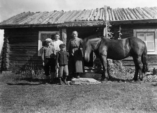 Man, kvinna och två pojkar med häst utanför sitt bostadshus. Dalarna, Lima socken, 1928. Fotograf: Edvard Larsson