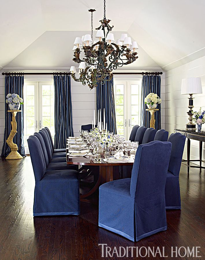 A pair of 1890s wrought-iron chandeliers hang above the custom table. Chairs are covered in a deep blue fabric. - Photo: Tria Giovan / Design: Kenneth Alpert