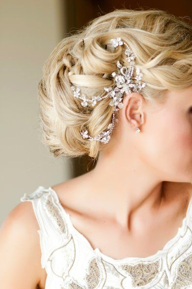 Her wedding hair was vintage inspired, soft waves swept into an elegant, asymmetrically focused bun with structured and unstructured curls featuring a vintage Swarozski hairpiece. Hair Stylist: Rebecca Biggers, Ashville, NC, Photography: Visio Photography, Marion, NC