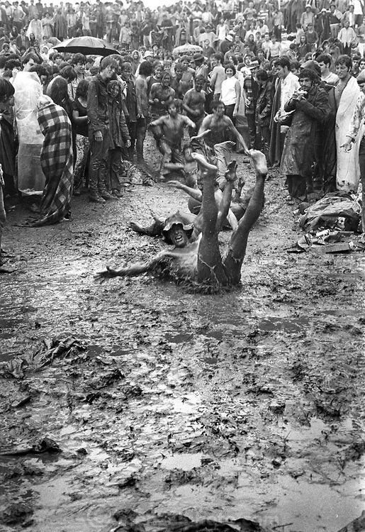 Woodstock concert goers sliding down a muddy hill (1969), photograph by Peter Menzel