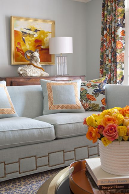 Gray and orange living room features gray walls framing window dressed in Schumacher Chiang Mai Dragon Aquamarine curtains situated behind gray, high-back sofa adorned with gray pillows with orange greek key trim layered over chiang mai dragon pillows atop cheetah print rug.