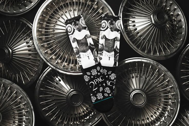 """The memory of Tupac Shakur, famed rap icon and pop culture phenomenon, lives on through Stance's new """"Legend""""  sock collection.  The late superstar was one of the music industry's best-selling artists until he tragically lost his life during an infamous Las Vegas shooting in 1996.  Tupac's image has been immortalized by two different sock designs; one featuring a photograph of Shakur showing off his signature """"Thug Life"""" abdomen tattoo and another that includes a front-facing bandana…"""