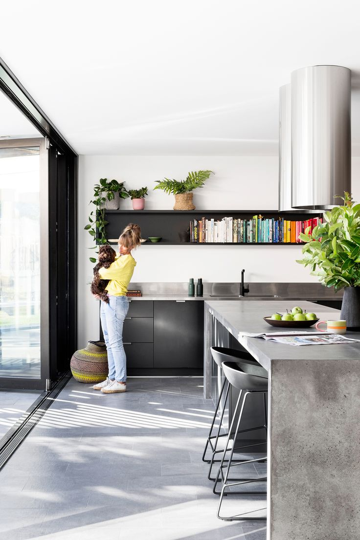 The layout of this kitchen, in an eco-friendly Melbourne home update, was designed with entertaining in mind; the concrete island faces the outdoor living space. Photography: Martina Gemmola | Styling: Ruth Welsby | Story: Australian House & Garden