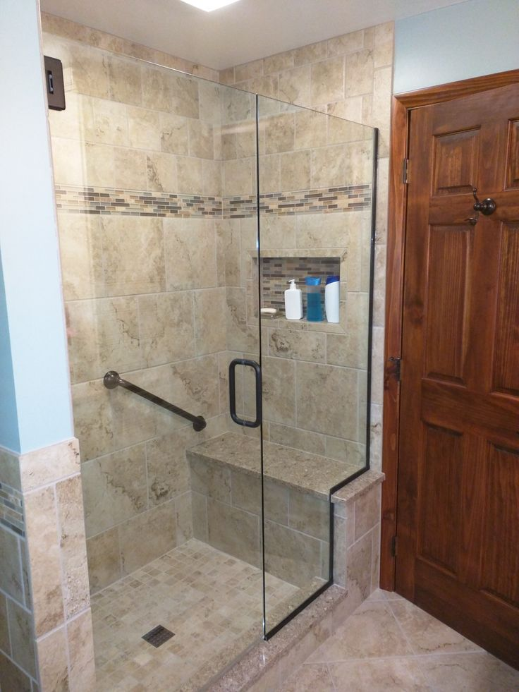 Tile shower with bench seat in Cambria quartz, Tiled wall niche, Moen grab bar, Euro shower door
