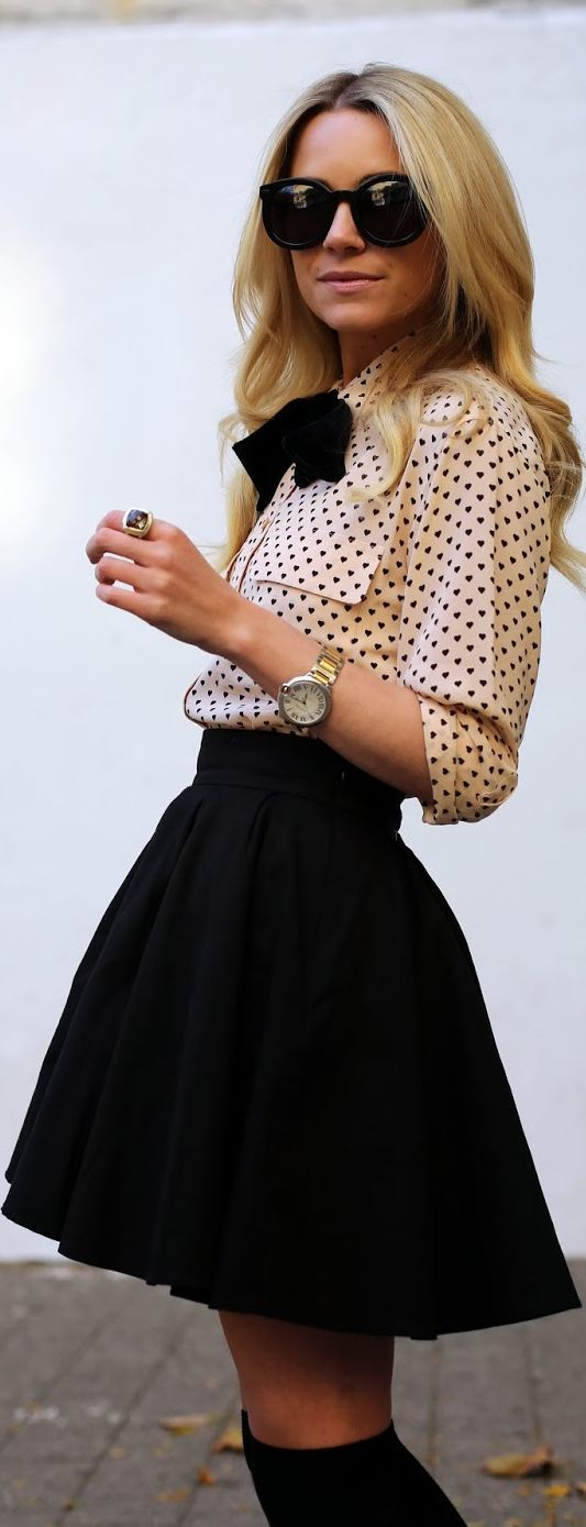 nude beige blouse with black polka dots and a high-waisted black full skirt