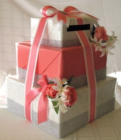 Corbeilles nuptiale 3 étages. Couleurs: Corail et blanc. Ornées de ruban mesh diamant et fleurs corail et blanches. Le tout selon les couleurs thème du mariage. Wishing well boxes 3 boxes. Coral and white. Decorated with diamond mesh ribbon and coral and white fowers. As per the theme colors of the wedding.