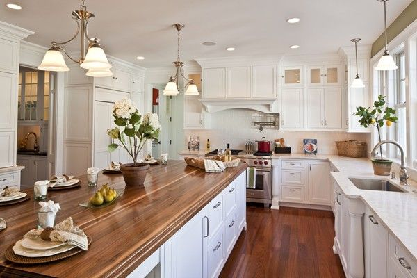 White kitchen units, dark wood floor with wood and pale granite/ marble work tops