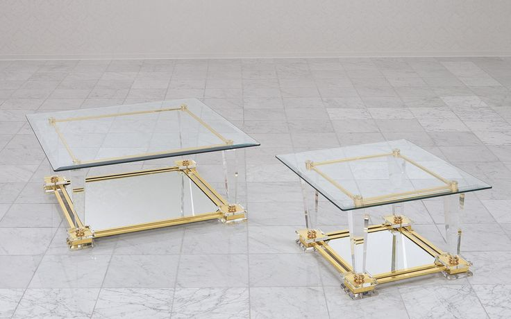 The coffee table Tosca has two inlaid plates of glass and a base made of metal and acrylic.