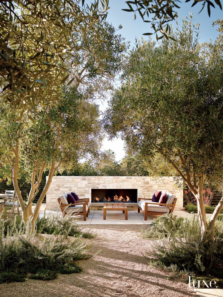 Trainor planted olive trees in the central courtyard, which features a fireplace wall with stone installed by Rodda's Hard Rock Masonry. Sessions upholstered the cushions of a sofa and armchairs, by Link Outdoor from De Sousa Hughes, with a Décor de Paris fabric. Pillows covered with a Perennials textile lend a colorful accent.
