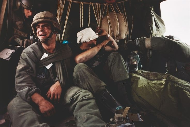 1991 - US Sergeant Ken Kozakiewicz (23), gives vent to his grief as he learns that the body bag at his feet contains the remains of his friend Andy Alaniz. 'Friendly fire' claimed Alaniz's life and injured Kozakiewicz. On the last day of the Gulf War they were taken away from the war zone by a MASH unit evacuation helicopter. (David Turnley)