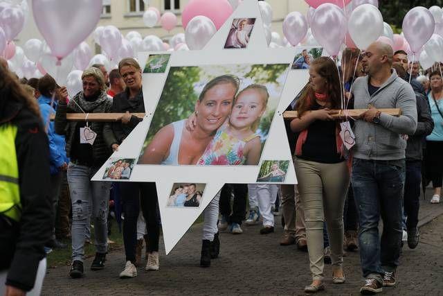 Familieleden en Delphine (roze sjaal), de boezemvriendin van mama Johanna, dragen een ster mee, met daarop foto's van de slachtoffers.-Joost De Bock