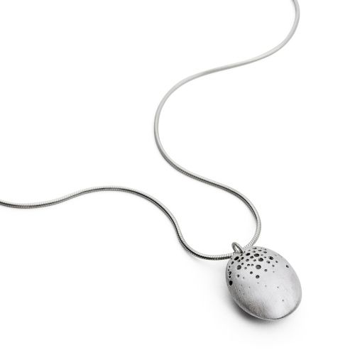 This sterling silver pendant features a hollow centre resembling a seed pod, the top of the pod reveals tiny drilled holes creating a cluster pattern that graduates down the pendant. This elegant design is neat and sits beautifully when worn a truly modern take on the organic form.