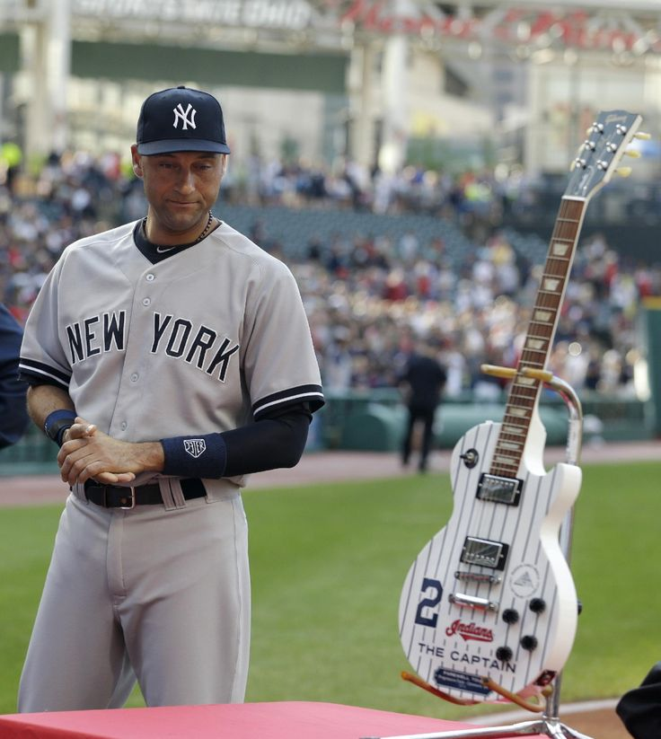 New York Yankees' Derek Jeter receives a pin-striped Les Paul guitar given to him by the Cleveland Indians organization before the Yankees played the Indians in a baseball game Thursday, July 10, 2014, in Cleveland. (AP Photo/Tony Dejak)