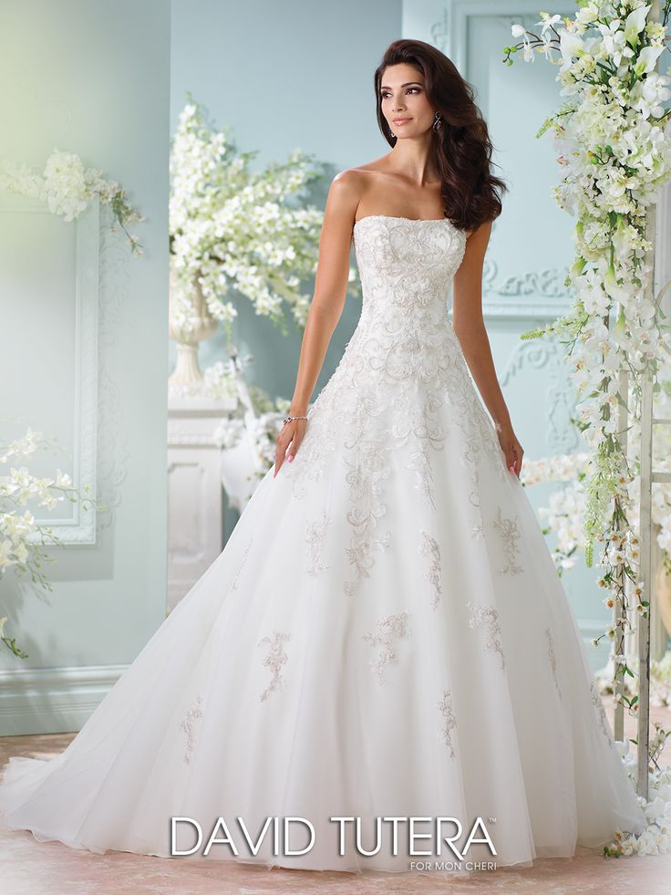 David Tutera for Mon Cheri - 116216 – Sunniva - Lace strapless wedding dress, tulle, organza and hand-beaded embroidered metallic Schiffli lace appliqué over satin full A-line gown with dropped waist, back covered buttons, skirt with cascading matching lace appliqués, chapel length train, detachable spaghetti and halter straps included. Sizes: 0 – 20, 18W – 26W Colors: Ivory/Tea Rose, Ivory, White