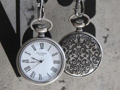 Antikt silverfärgat vintageur med blomster på baksidan.  Ett svart och ett vitt flätat läderband medföljer.    Diameter: 5cm