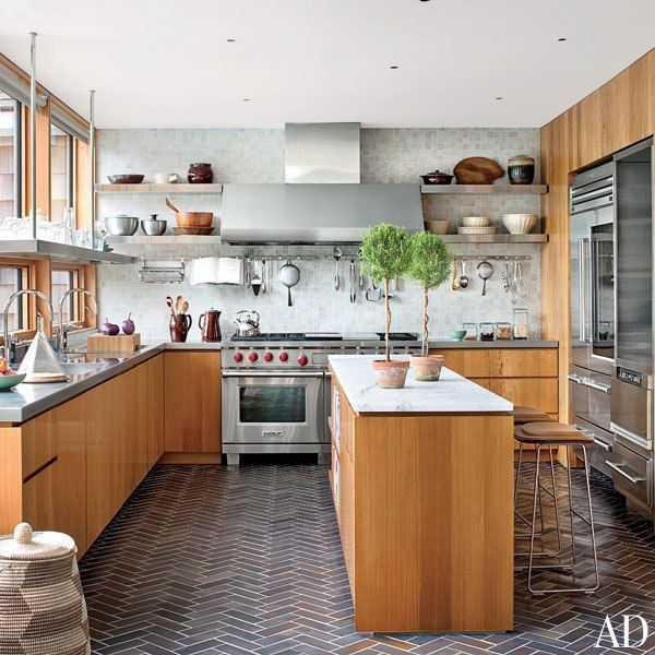 The wood-and-stainless-steel kitchen of a laid-back summer house features Urban Archaeology floor tiles in a herringbone pattern.