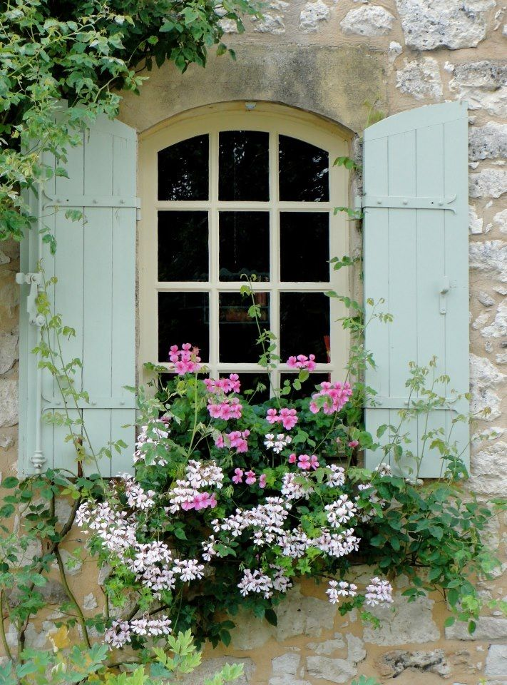 Stone House with Vintage Shutters and Geraniums in a Window Planter.