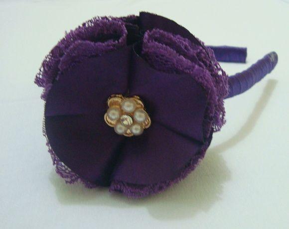 Tiara revestida em fita roxa com flor em cetim e renda com lindo botão decorativo, que vai deixar sua princesa encantada. R$ 18,90