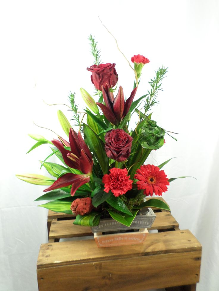 Floral table arrangement inside a crate. A beautiful mix of roses, lilies and gerbera's. Created by florist ilene