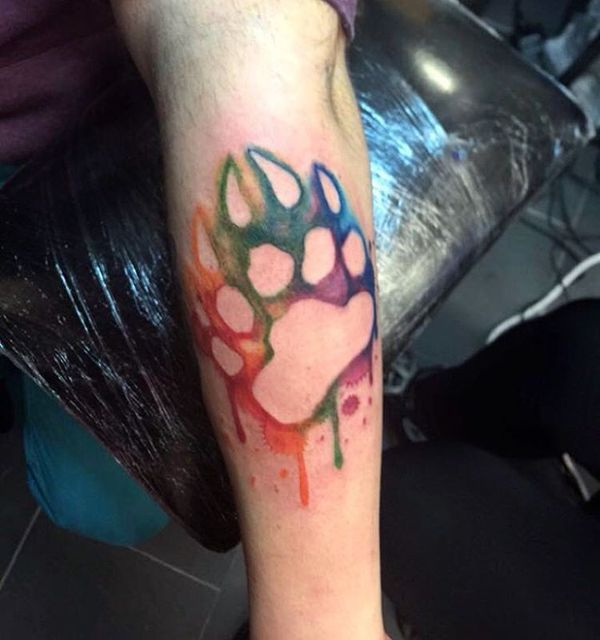 watercolor bear paw tattoo on forearm