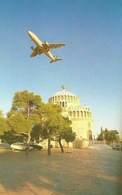 Olympic Airways plane  flying over the church of St. Konstantine & St. Helen in Glyfada
