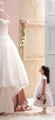Flower girl looking at wedding gown