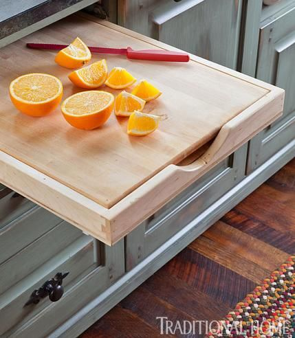 A wooden cutting board pulls out from under the counter, and lifts up to store other cutting boards. - Traditional Home ® / Photo: Emily Minton Redfield / Design: Dawn Bergan