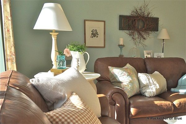 Here is a cottage look done with brown leather sofas, unusual but looks good.  I think the blue walls and the white accents help.