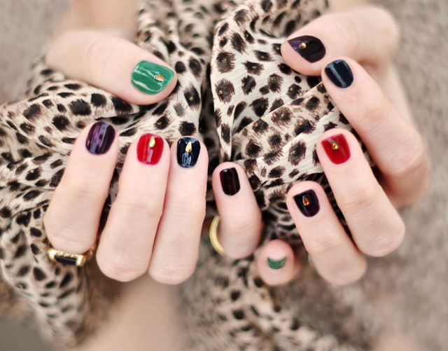 Uñas de diferentes colores (en este caso tonos otoñales) con una lágrima de pedrería