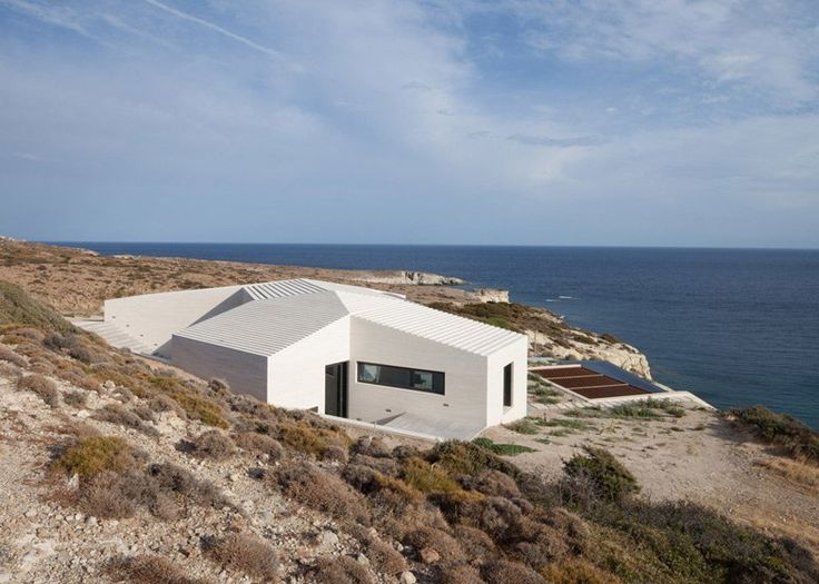 Ridged limestone house by decaArchitectureon the edge of a cliff on the Greek island ofMilos.