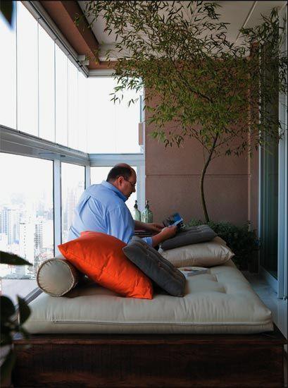 O morador aproveita a luminosidade natural da varanda para ler. Projeto de Zi...