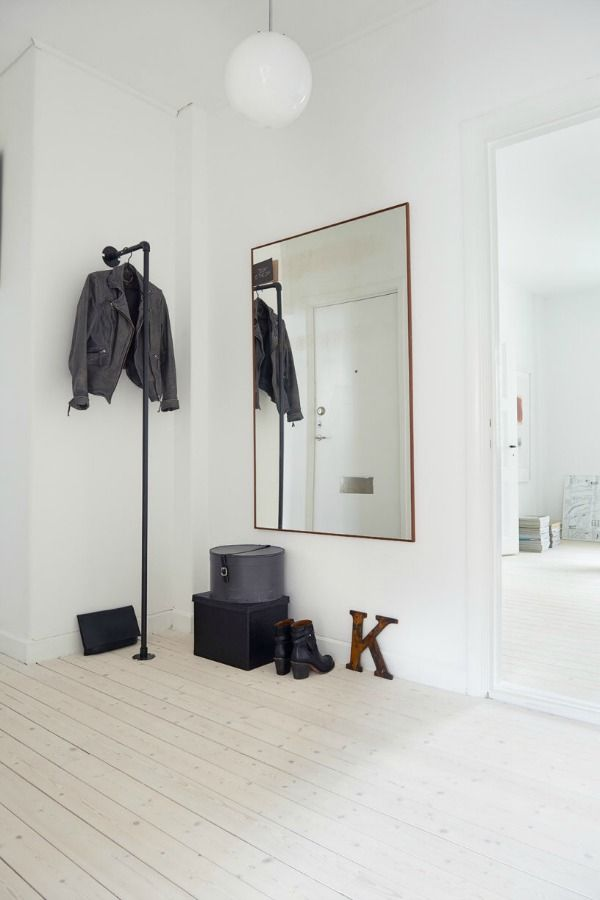 minimalistische-gang-hal met witte muur, lichte vloer en spiegel