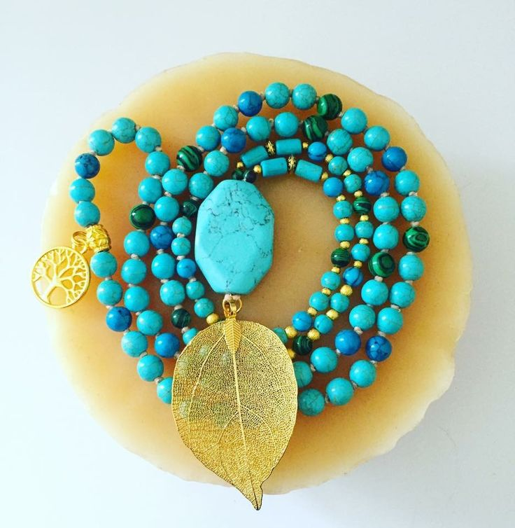 """108 bead hand-knotted Mala with 6/8mm Turquoise, Magnesite and Malachite beads. Gold accents and a beautiful filigree leaf focal, with a tree of life charm on the back end. Hangs at about 22"""""""