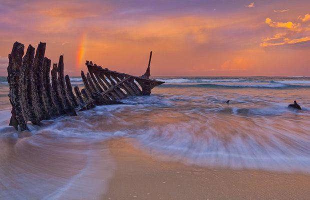 """The last remaining section of the SS Dicky on Dicky Beach, Queensland. """"A late afternoon thunderstorm passed leaving us with a half rainbow,"""" says photographer Erin Cole. """"The image was taken using several slide grad filters and a circular polarising filter."""" <3 the rainbow"""