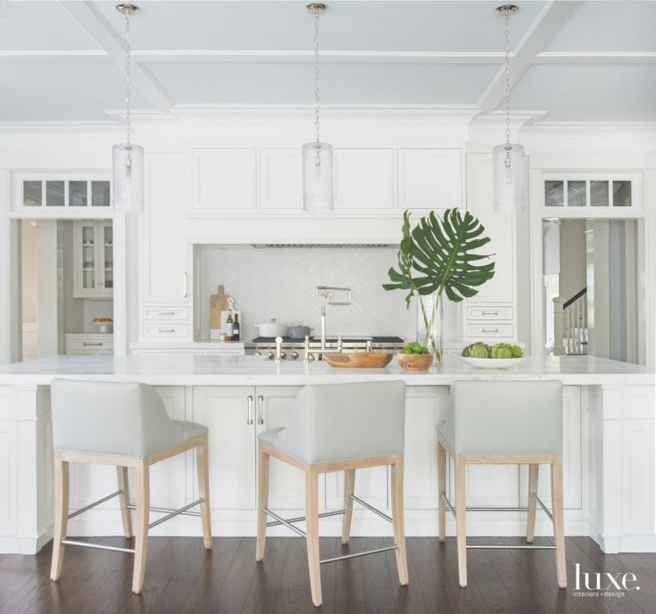 A trio of glass pendants by Juliska lights the kitchen island, which is topped with honed Danby marble from Paul's Marble Depot; the Jessica Charles counter stools, featuring a driftwood finish, are upholstered in Schumacher vinyl. The kitchen cabinetry is by V & A Construction, and the farmhouse sink is by Franke.