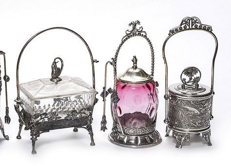 A group of three Victorian pickle castors including a marked Pairpoint embossed metal caddy with fork hanger, a shaded cranberry barrel form with molded body, and a rectangular shaped castor with etched glass lid and pickle finial.