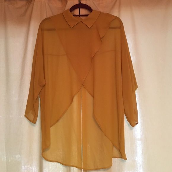 Mustard yellow sheer high low collared blouse Gold colored sheer high low blouse.  The front crossover with a high  triangle opening.  The back is low rounded seam and button up in the back.  The sleeves are bat winged.  The collar tone down the shirt, but it's so cute with skinny jeans and boots. Lost April Tops Blouses