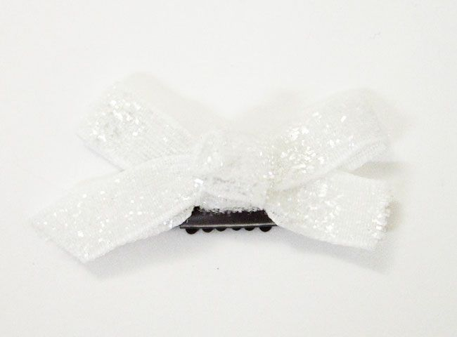 Glittery velvet boutique bow attached to a mini latch clip.