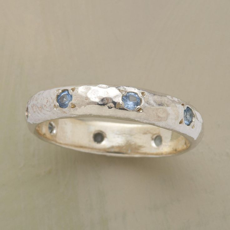 BLUE TOPAZ ETERNITY BAND -- Adding to the sparkle of faceted topaz encircling the perimeter of this blue topaz eternity band is the hammered sterling silver band. Handcrafted exclusively for Sundance. Whole and half sizes 5 to 9-1/2.