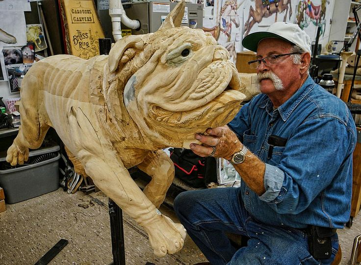 A volunteer carver works on a sculpture of a bulldog at the Albany Carousel Project Workshop in Albany, Oregon | Flickr