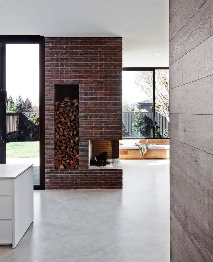 Fireplace Design Idea - 6 Different Materials To Use For A Fireplace Surround // Deep red bricks have been used to create the fireplace surround that incorporates wood storage.