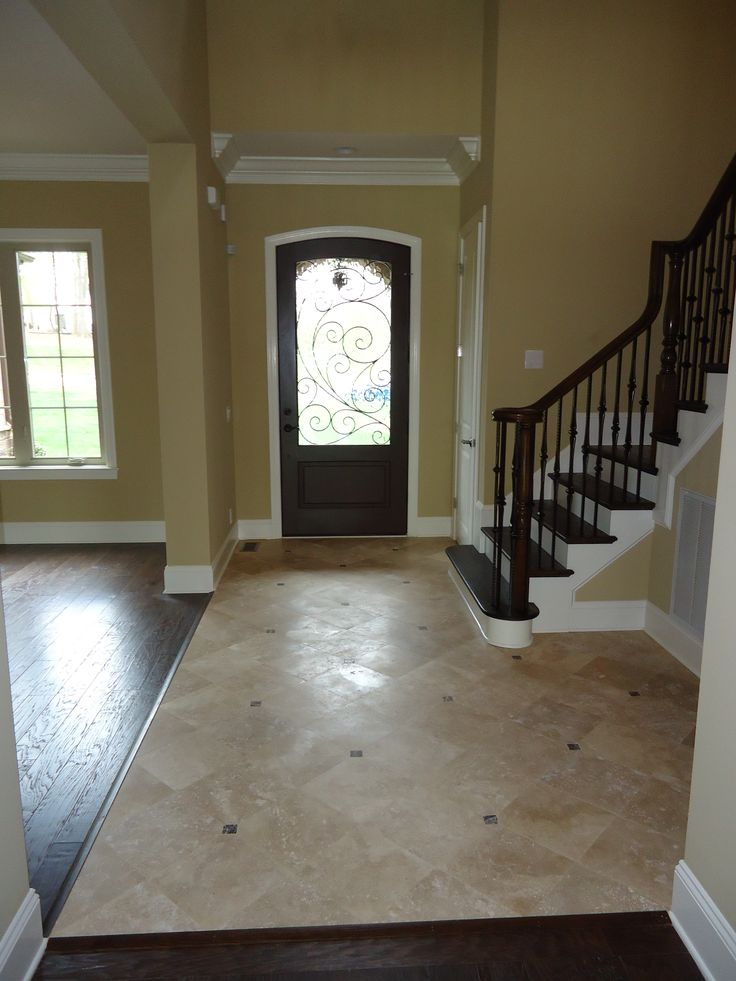 The saddlebrook foyer with travertine flooring and wrought - What is a foyer ...