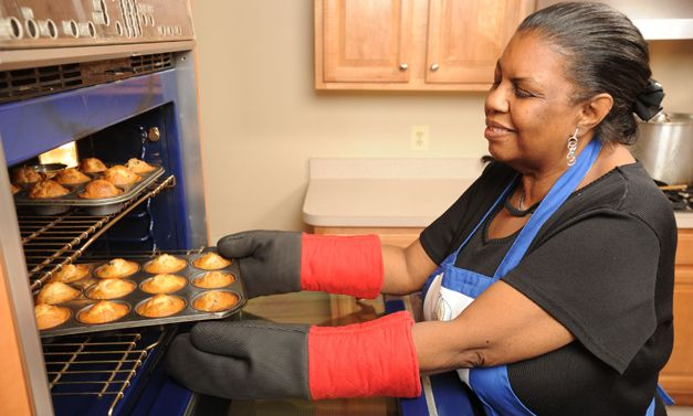 Senior student removing muffins from oven